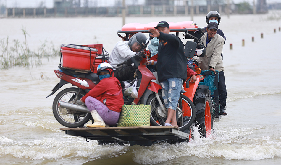 Residents are carried on a forklift truck to dry land through flood waters brought by heavy rain from Typhoon Vamco
