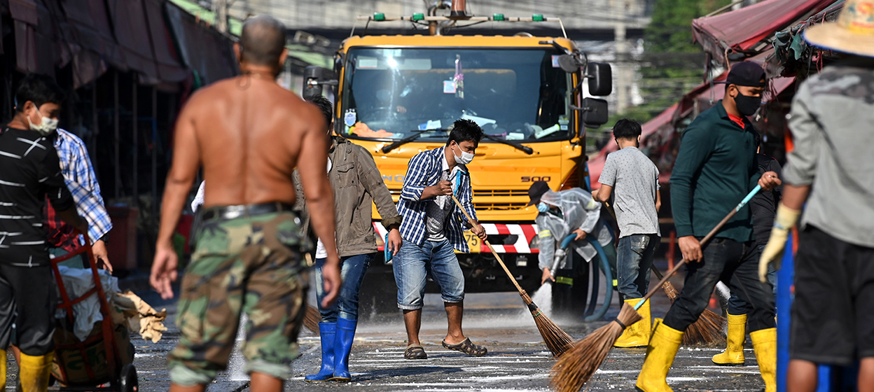 Market workers and volunteers clean up around Klong Toey fresh market