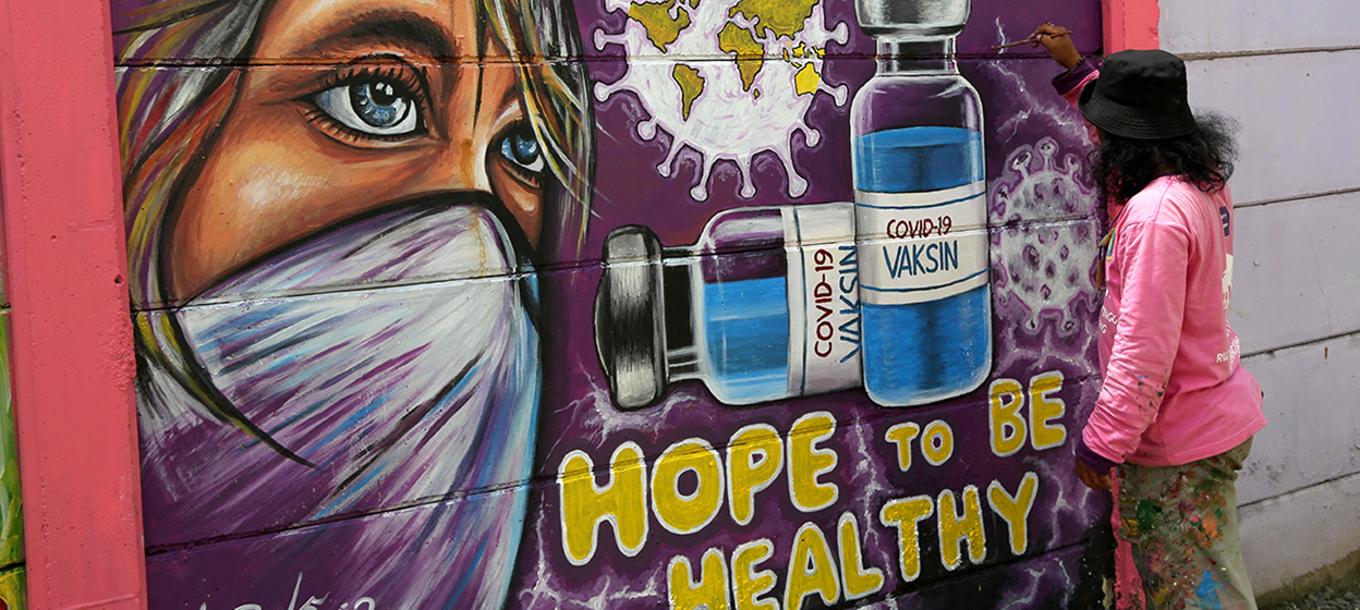 A mural of the Covid-19 vaccine along a street in Tangerang