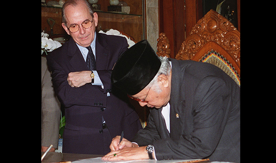 Indonesian President Suharto signs a new letter of agreement as IMF Director-General Michel Camdessus looks on