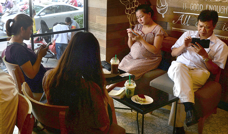 People using smartphones to check the Internet over wifi at a coffee shop in Hanoi.