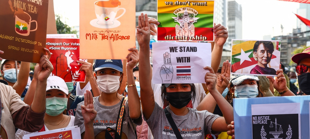 "Pro-democracy protesters holding signs relating to the ""Milk Tea Alliance"" and the current situation in Myanmar"