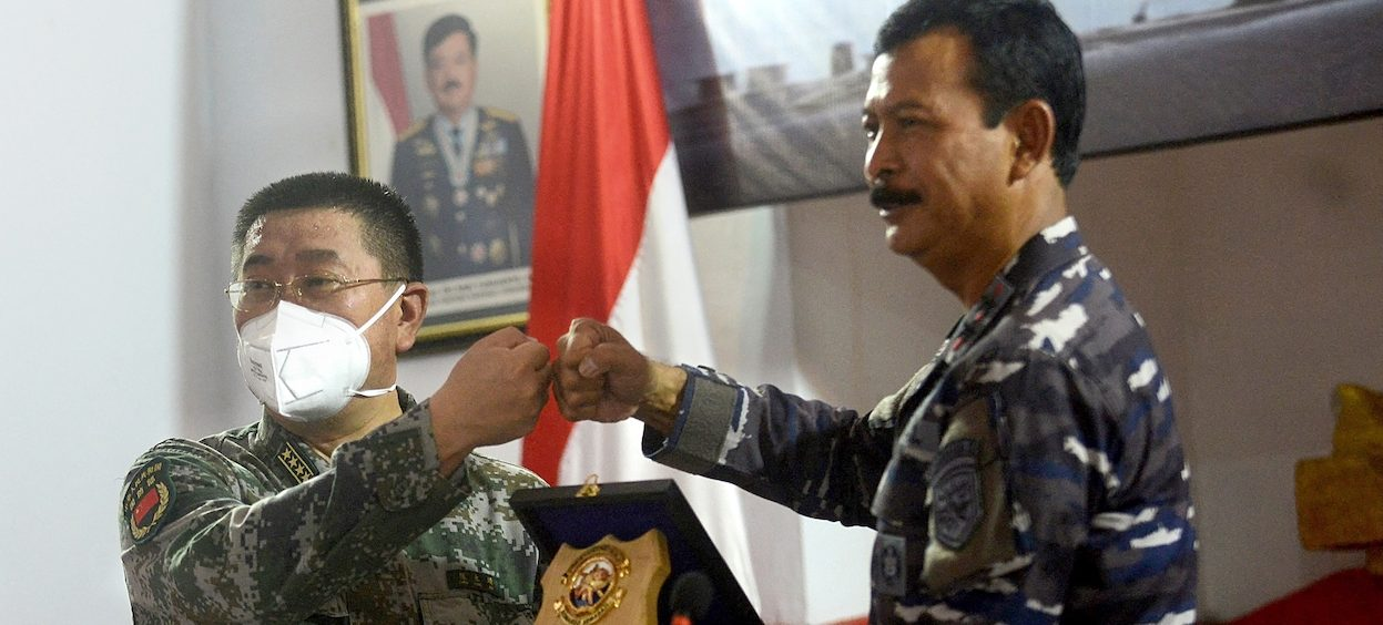 Rear Admiral Iwan Nurcahyanto (L) of Indonesia gives a souvenir to Colonel Chen Yongjing of China after their joint press conference on Lanal base in Denpasar, on Indonesian resort island of Bali, on 18 May, 2021. (Photo: Sonny TUMBELAKA/ AFP)