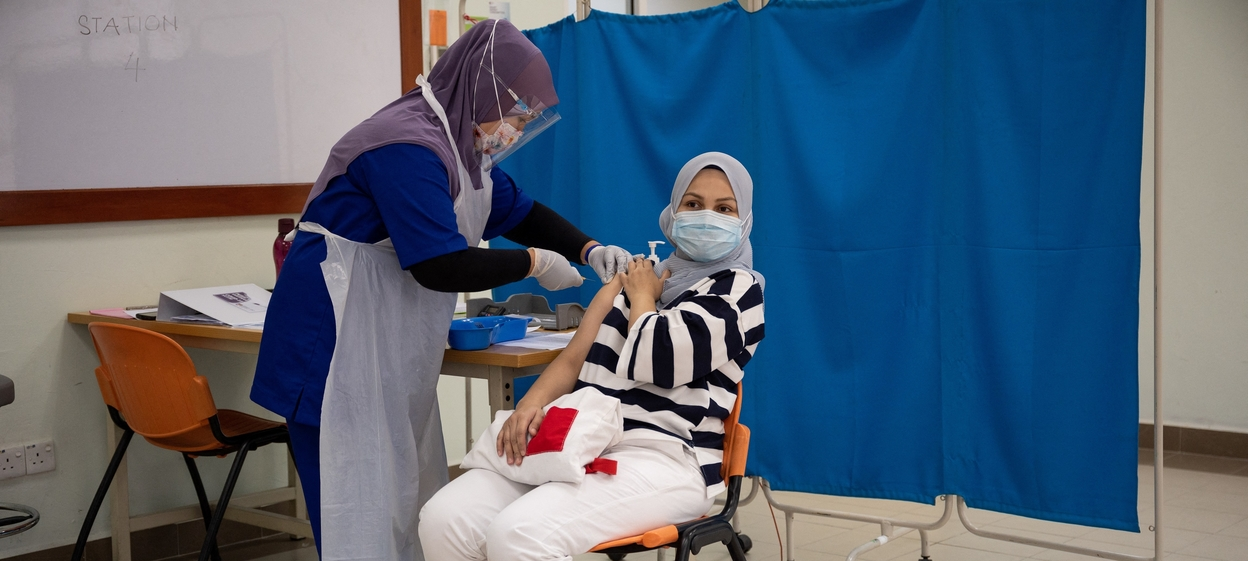 A medical staff administers the Pfizer-BioNTech COVID-19 coronavirus vaccine to a health personnel at the Hospital UiTM in Sungai Buloh.