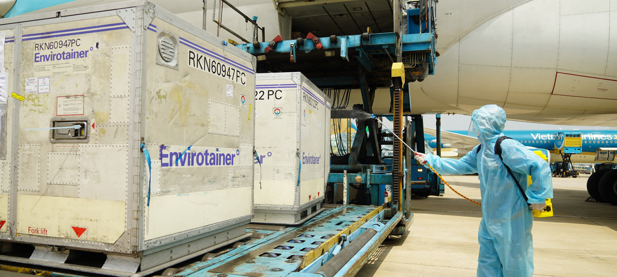 A health official sprays disinfectant on the first batch of AstraZeneca/Oxford Covid-19 coronavirus vaccine shipment