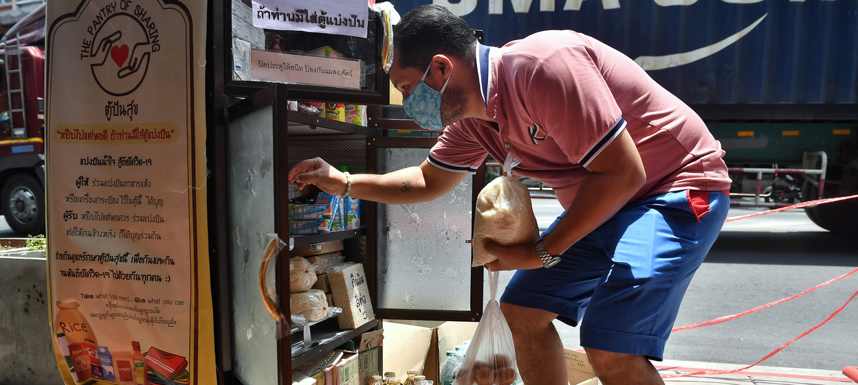 """A man collects goods donated by the public at a """"Pantry of Sharing"""" in Bangkok"""