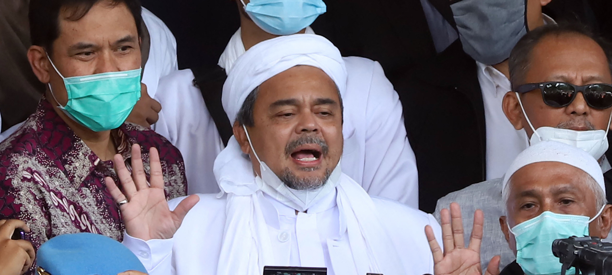 Indonesian Muslim cleric Rizieq Shihab (centre) surrounded by his supporters upon arrival at the police headquarters in Jakarta.