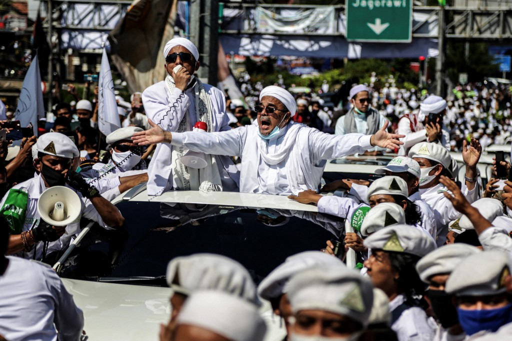Muslim cleric Rizieq Shihab gestures to supporters as he arrives to inaugurate a mosque in Bogor.